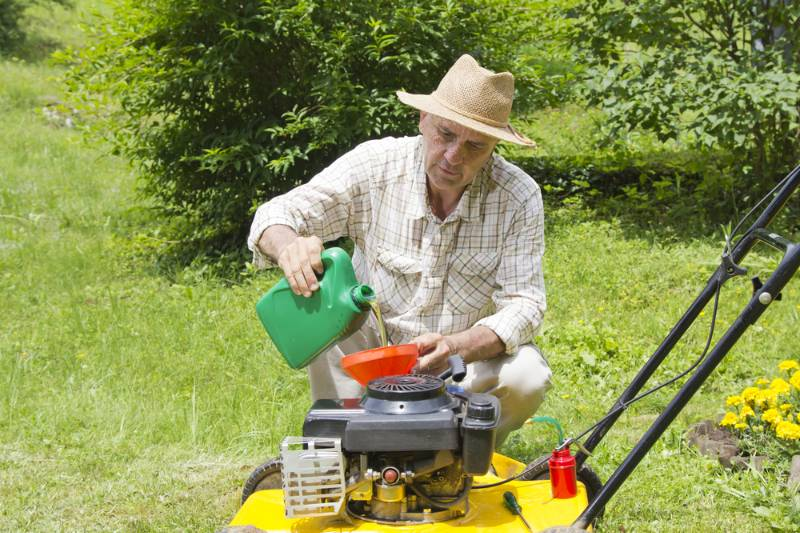 mid age man adding oil lawn | Lawn Mower Repair: Common Problems And How To Fix Them